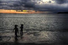 Het avondstrand, mensen heeft pret in de oceaan bij zonsondergang Stock Foto's