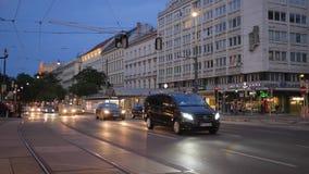 Het avondverkeer, veel van auto met het branden van koplamp gaat op weg voorbij het inbouwen van stad stock footage