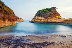 Het Avontuurtjestrand van beroemde Kanaald 'met mooie rotsachtige kustlijn in verbazende blauwe Ionische Overzees bij zonsopgang  royalty-vrije stock afbeelding