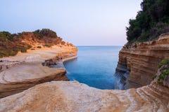 Het Avontuurtjestrand van beroemde Kanaald 'met mooie rotsachtige kustlijn in verbazende blauwe Ionische Overzees bij zonsopgang  stock foto's