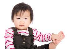Het Aziatische babymeisje raakt haar been Stock Foto's