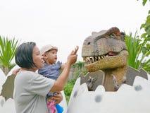 Het Aziatische babymeisje, samen met haar tante, geniet van kijkend en wat betreft een dinosaurus stock afbeelding