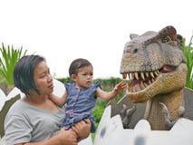 Het Aziatische babymeisje, samen met haar tante, geniet van kijkend en wat betreft een dinosaurus royalty-vrije stock fotografie