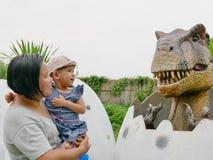 Het Aziatische babymeisje, samen met haar tante, geniet van kijkend en wat betreft een dinosaurus stock fotografie