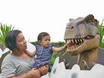 Het Aziatische babymeisje, samen met haar tante, geniet van kijkend en wat betreft een dinosaurus stock afbeeldingen