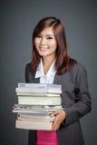 Het Aziatische bedrijfsmeisje houdt vele boeken Stock Foto's