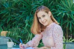 Het Aziatische bedrijfsvrouwen glimlachen werkend en schrijvend een boek en che royalty-vrije stock fotografie