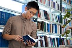 Het Aziatische boek van de mensenlezing in bibliotheek Stock Foto's