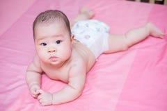 Het Aziatische chagrijnig blike chagrijnig blik van het babymeisje op roze bed Royalty-vrije Stock Afbeeldingen
