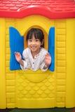 Het Aziatische Chinese meisje spelen in stuk speelgoed huis Stock Fotografie