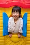 Het Aziatische Chinese meisje spelen in stuk speelgoed huis Stock Foto's