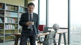 Het Aziatische collectieve uitvoerende ontspannen in bureau stock videobeelden