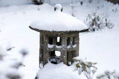 Het Aziatische concrete die ornament van het tuinstandbeeld in sneeuw wordt behandeld royalty-vrije stock fotografie