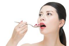 Het Aziatische de lepel van het vrouwengebruik nemen talrijk van geneeskundepil stock afbeelding