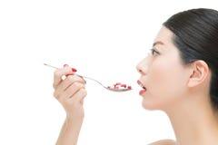 Het Aziatische de lepel van het vrouwengebruik nemen talrijk van geneeskundepil royalty-vrije stock fotografie