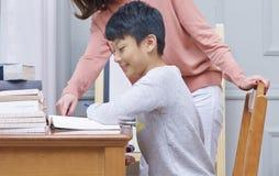 Het Aziatische de tiener van de moederhoede lezing & schrijven Stock Foto's
