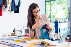 Het Aziatische de vrouw van de manierontwerper naaien in haar workshop stock foto