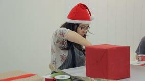 Het Aziatische donkerbruine vrouwenwerk met verpakkings nieuw jaar stelt binnen voor stock video
