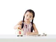 Het Aziatische geld van de meisjebesparing in een spaarvarken Geïsoleerdj op witte achtergrond stock afbeeldingen