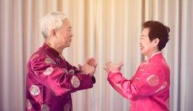 Het Aziatische hogere paar viert Chinees nieuw jaar in rood traditioneel kostuum stock foto