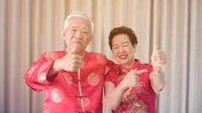 Het Aziatische hogere paar viert Chinees nieuw jaar in rood traditioneel kostuum royalty-vrije stock foto