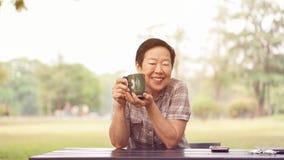 Het Aziatische hogere vrouw glimlachen in park met koffiekop, ontspant daarna Royalty-vrije Stock Foto's