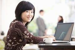 Het Aziatische Huis van Onderneemsterusing laptop at Stock Afbeeldingen