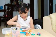 Het Aziatische jong geitje spelen met deeg Stock Foto's