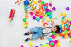 Het Aziatische jong geitje spelen met stuk speelgoed stock foto