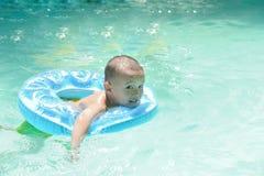 Het Aziatische jong geitje zwemmen stock fotografie