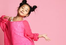 Het Aziatische jong geitjemeisje in roze sweater, witte broek en grappige broodjes is op manier stelt en glimlachen vrije tekstru stock foto
