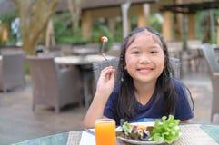 Het Aziatische jonge geitje geniet van om vegatable salade te eten royalty-vrije stock afbeelding