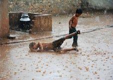 Het Aziatische jonge geitje viel op een gladde grond die in zware regen lopen Stock Foto