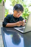 Het Aziatische jonge meisje typen op smartphone stock afbeelding