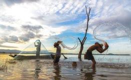 Het Aziatische jongen en meisjes spelen in de rivier met visser, in de ochtendzonsopgang stock foto
