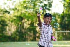 Het Aziatische jongen het spelen stuk speelgoed van het ballonkanon Stock Afbeelding