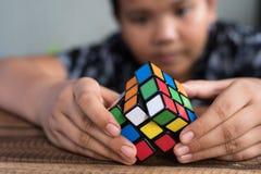 Het Aziatische jongen spelen met rubik` s kubus jongen die raadsel oplossen stock foto's