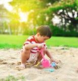 Het Aziatische jongen spelen in speelplaats stock foto