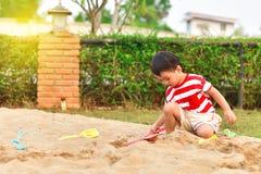 Het Aziatische jongen spelen in speelplaats stock afbeelding