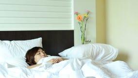 Het Aziatische kielzog van de vrouwentiener omhoog en ontspanning in bed stock videobeelden