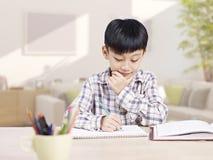 Het Aziatische kind bestuderen stock fotografie