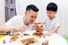 Het Aziatische kind en vader spelen met houten blokken in de ruimte thuis Een soort onderwijsspeelgoed voor kleuterschool en kleu royalty-vrije stock foto