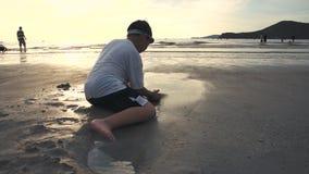 Het Aziatische kind heeft pret het graven in het zand Jonge jongen die op strand genieten van stock videobeelden