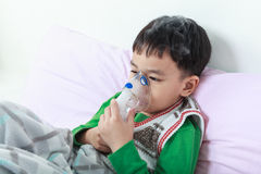 Het Aziatische kind houdt een inhaleertoestel van de maskerdamp voor behandeling van astma stock foto's