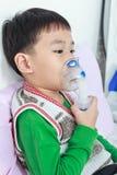 Het Aziatische kind houdt een inhaleertoestel van de maskerdamp voor behandeling van astma royalty-vrije stock fotografie