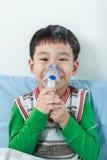 Het Aziatische kind houdt een inhaleertoestel van de maskerdamp voor behandeling van astma royalty-vrije stock afbeeldingen