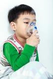 Het Aziatische kind houdt een inhaleertoestel van de maskerdamp voor behandeling van astma royalty-vrije stock foto's