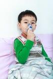 Het Aziatische kind houdt een inhaleertoestel van de maskerdamp voor behandeling van astma stock afbeelding