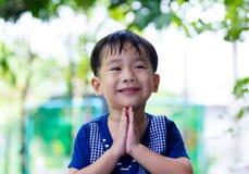 Het Aziatische kind zette de palmen samen van de handen in begroeting Stock Foto's