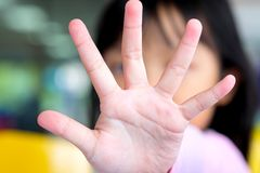 Het Aziatische kindmeisje hief zijn hand aan blok op stock foto's